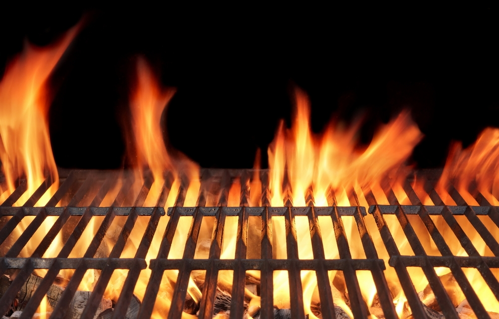 A picture of a bbq grill with flames about to cook some Ribfest pulled pork.